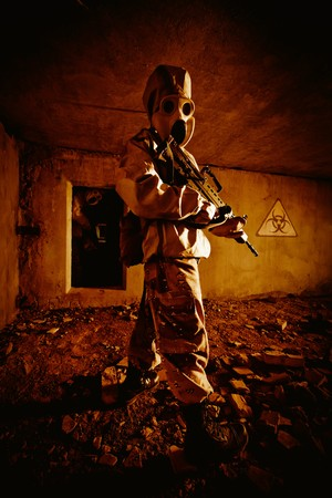 Two soldiers with the rifles in the gas masks and protective clothes in the old bunker photo