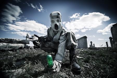 riesgo biologico: Dos soldados en las m�scaras de gas y ropa protectora est�n probando un arma biol�gica en el fondo de ruinas.