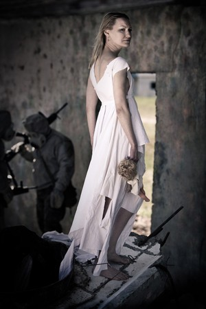 Sad girl in white dress with the doll on the ruined building background. Two soldiers in the gas masks on the background.  photo