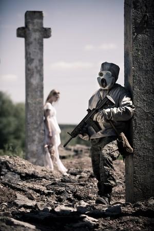 mask gas: Soldado de la m�scara de gas con el fusil en el primer plano, chica en blanco con la mu�eca Cruz cerca sobre el fondo