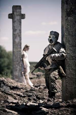 camouflage woman: Soldier in the gas mask with the rifle on the foreground, girl in white with the doll near cross on the background Stock Photo