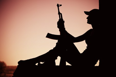 Silhouette of a girl with the machine gun in the doorway. photo