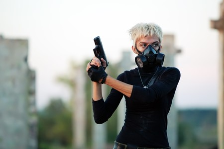 Blond woman in the gas mask with the pistol on the ruined background. photo