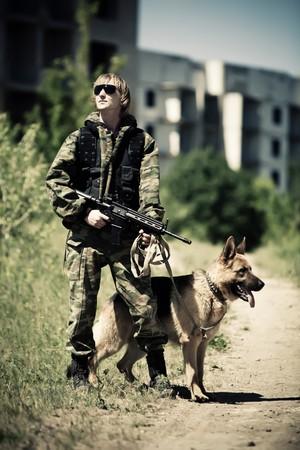perro policia: Soldado con el perro en el fondo de la ciudad en ruinas. Proceso cruzado con el estilo.  Foto de archivo