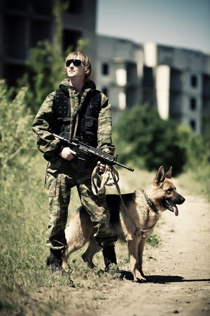 Soldier with the dog on the ruined city background. Cross process styled.