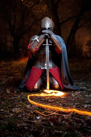 cavaliere medievale: Khight medievale nella corazza con la spada. Ritratto nella foresta. Archivio Fotografico