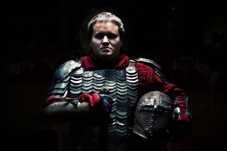caballero medieval: Caballero medieval en la armadura con la espada y el casco.