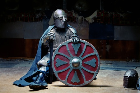 Medieval knight in the armor with the sword and shield. Portrait in the shadows.