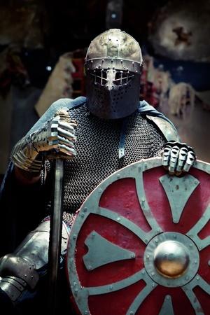 caballero medieval: Caballero medieval en la armadura con la espada y el escudo. Retrato en las sombras.
