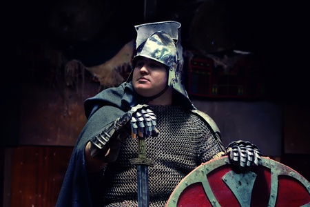 Medieval knight in the armor with the sword and shield. Portrait in the shadows. photo