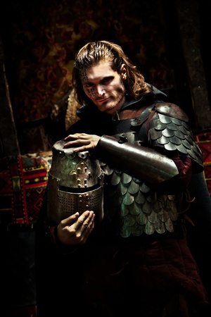 Medieval knight in the armor with the helmet. Portrait in the shadows. Archivio Fotografico