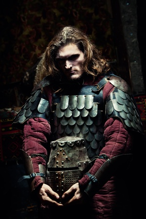 Medieval knight in the armor with the helmet. Portrait in the shadows. Standard-Bild