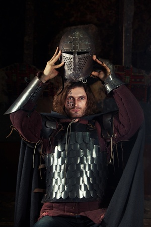 protective suit: Medieval knight is going to wear a helmet. Portrait in the shadows.