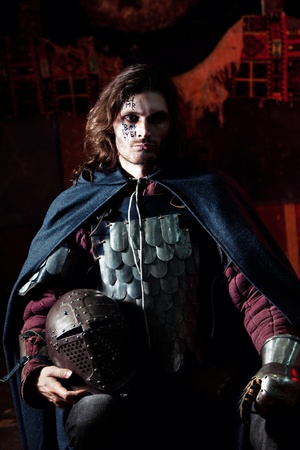 Medieval knight in the armor with the helmet. Portrait in the shadows. Stock Photo