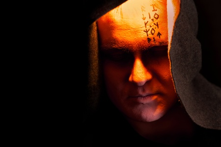 Mystery monk with the runes on the face. Portrait in the shadows. Stock Photo