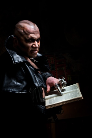 disdain: Black Magician in the leather raincoat is reading a book. Stock Photo