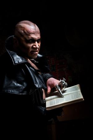 desprecio: Mago negro en el impermeable de cuero est� leyendo un libro.