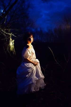 Girl in vintage white dress lost in the dark forest. Stock Photo - 8348168
