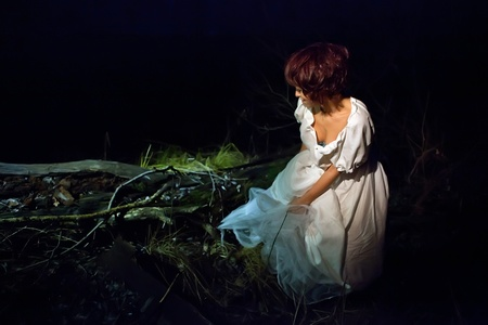 Girl in vintage white dress lost in the dark forest. photo