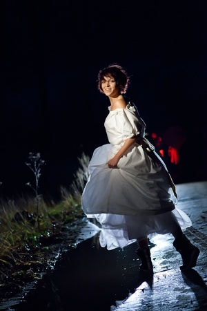 Girl in vintage white dress find the road in the dark forest. photo