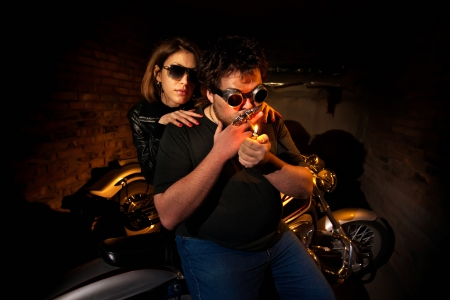 Pretty couple is sitting on the motorcycle. Brick wall on the background. photo