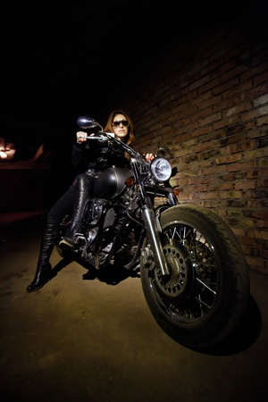 Pretty woman is sitting on the motorcycle. Brick wall on the background.