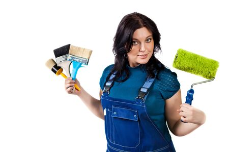 Pretty woman in coveralls with paintbrushes and roller. Isolated on white background. photo
