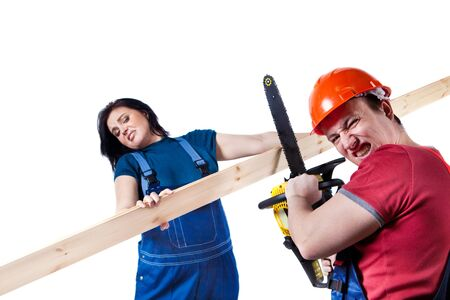 Furious man in helmet is going to cut the linings with the chainsaw, woman is holding linings. photo