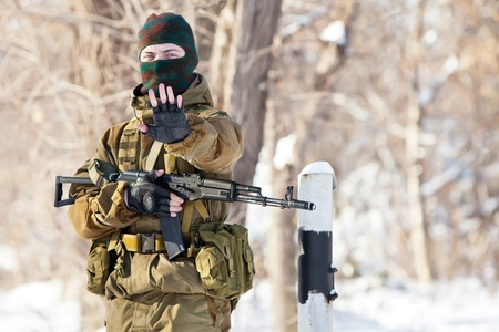 Russian soldier in winter uniform with machine gun on the forest background. photo