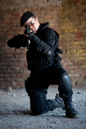 combative: NATO soldier with M4 rifle on the brick wall background.
