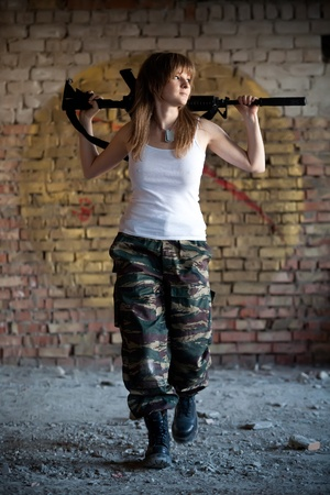 Walking mercenary woman with the rifle on the brick wall background photo