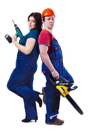 Man and woman with the chainsaw and drill are standing back to back. Isolated on white. photo