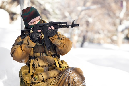 Russian soldier in winter uniform with machine gun on the forest background. Stock Photo