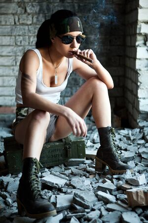 mercenary: Mercenary woman with a big cigar on the brick wall background. Stock Photo