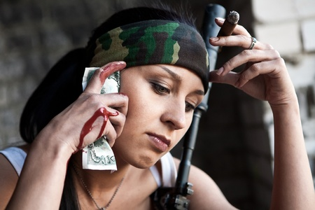cigar smoking woman: Pretty mercenary woman with the jammed dollar bill on the one hand and cigar in another. Stock Photo
