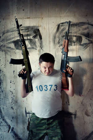 mercenary: Mercenary with two submachine guns on the painted wall background Stock Photo