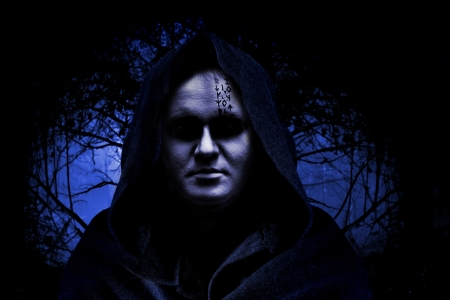 Man in hood on the spooky forest background. photo