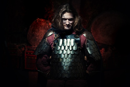protective suit: Powerful knight in the armor with the sword. Dark background. Stock Photo