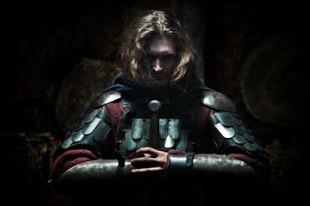 cavaliere medievale: Potente cavaliere in armatura con la spada. Sfondo scuro.