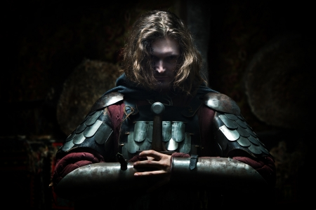 warrior: Powerful knight in the armor with the sword. Dark background. Stock Photo