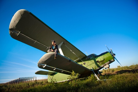 Smoking pilot in the helmet is sitting on the wing of a vintage plane. Stock Photo - 10327908
