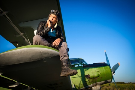 Smoking pilot in the helmet is sitting on the wing of a vintage plane. Standard-Bild