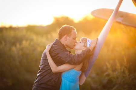 Beautiful couple is kissing under the vintage plane. Sunset on the background.