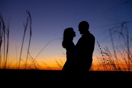 Pretty couple in the meadow on the sunset background. Standard-Bild