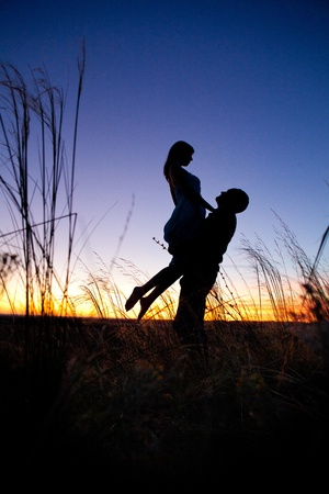 desires: Pretty couple in the meadow on the sunset background. Stock Photo