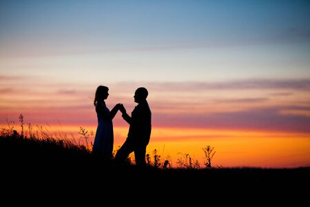 engagement silhouette: Pretty couple in the meadow on the sunset background. Stock Photo