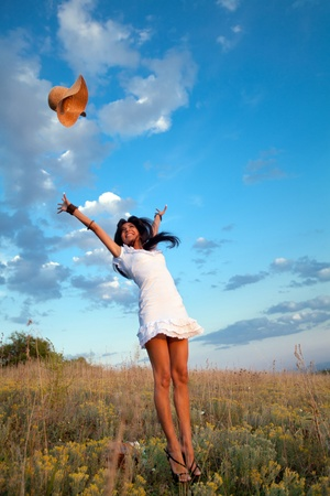 Attractive yong woman is jumping and throwing her hat. Rural evening background. Archivio Fotografico