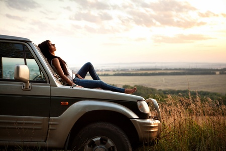 Attractive yong woman is laying on the cars hood and looking at sunset. Rural evening background. Stock Photo