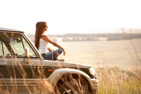 Attractive yong woman is sitting on the car's hood and looking at sunset. Rural evening background. Archivio Fotografico