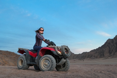 Pretty positive girl on atv on the desert sunrise background photo